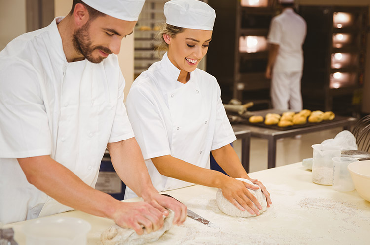 bakers kneading dough trainee