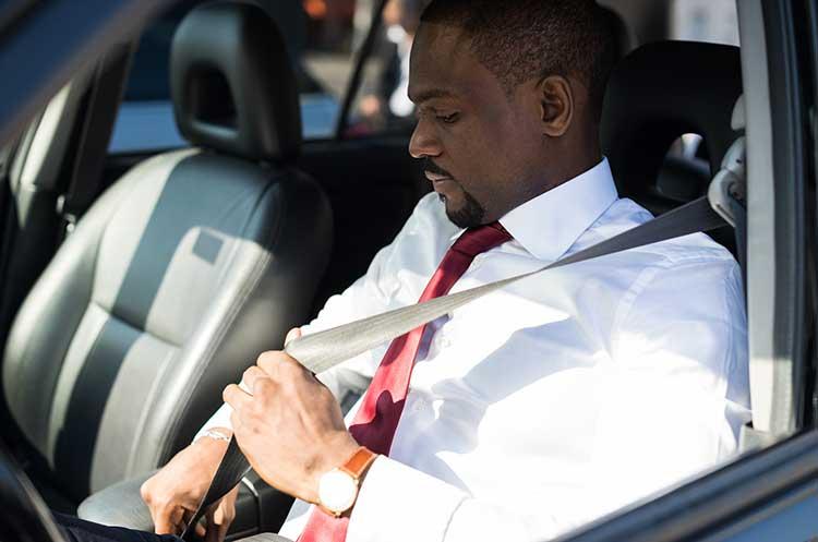 business man buckling seatbelt